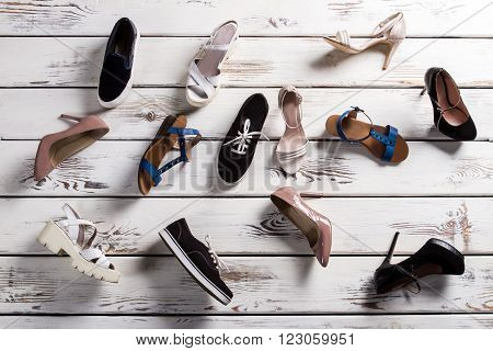 Different shoes laying on floor. Lady's footwear on wooden background. Mess on shoe store's floor. Shoes fell from shelf.