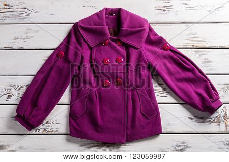Lady's purple fleece coat. Purple coat on white shelf. Woman's coat with folded collar. Bright-colored coat for women.