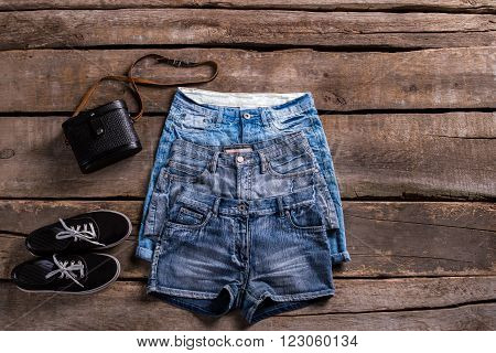 Lady's different length denim shorts. Different shorts on old table. Classic female shorts with keds. Black shoes and vintage shorts.