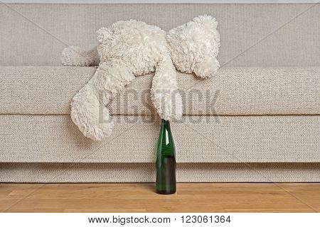White Teddy bear is laying on edge of the sofa with the bottle in it's hand