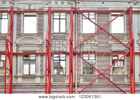 restoration facade of old house, red steel structure forms to avoid collapsing