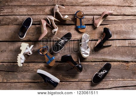 Female casual and luxury shoes. Woman's shoes on aged floor. Footwear laying on old table. So many different shoes.