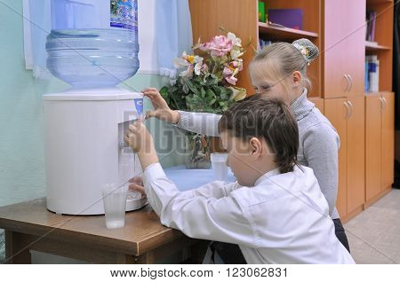 Murmansk, Russia - November 29, 2012, Children collect water from the cooler in the classroom, Murmansk