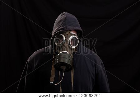 Man In Black Clothes Wearing A Classic Gas Mask Over A Dark Background