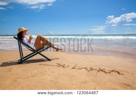 Young woman smiling lying in straw hat with pineapple juice on beach