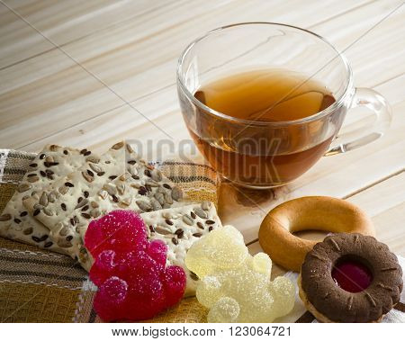 The composition of the tea beverage in a large bowl and some sweets on the table. Candied fruit jelly, cereal biscuits, bagels and biscuits with marmalade.