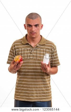 Man Offering Pill In One Hand And Apple In Another. Copy Space Boxes With Supplements. Concept Of Na