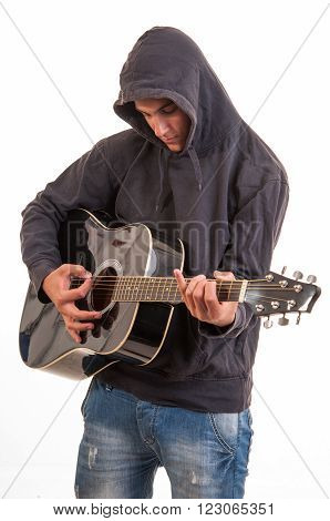 Sad Teenager In Hoodie Playing Acoustic Guitar. Trying To Write A Song About Teenage Problems