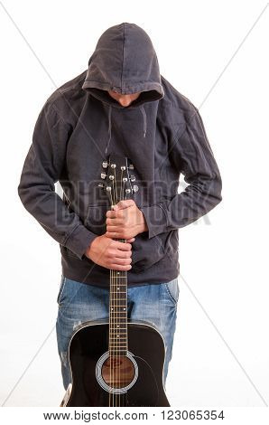 A Young Boy In Hoodie With His Head Down Standing And Holding His Guitar
