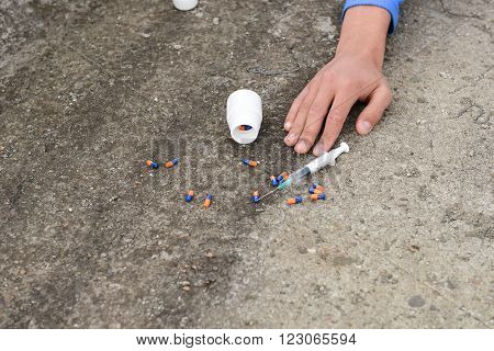 Hand Of A Drug Addict Near A Syringe And Pills. Simulate A Suicide