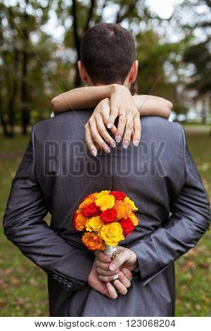 Women's arms around a man's head in the park on a date