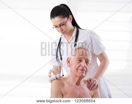 Young pretty practitioner massaging senior man with plastic roller massager