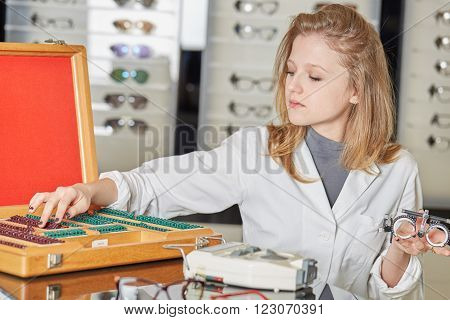 young beautiful blond optometrist showing new eyeglass