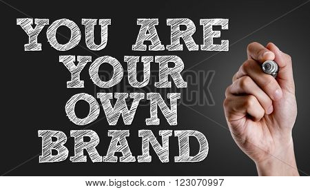 Hand writing the text: You Are Your Own Brand