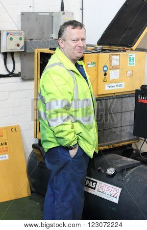 PORTSMOUTH, ENGLAND, 15TH MARCH 2016: An engineer working on a compressor in portsmouth, england 15th march 2016