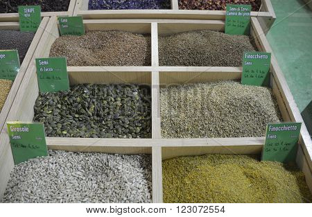 A selection of died ground spices on an Italian spice market stall - linseed pumpkin seeds sunflower seeds cumin seeds fennel seeds and dried fennel petals. The focus is on the centre of the display.