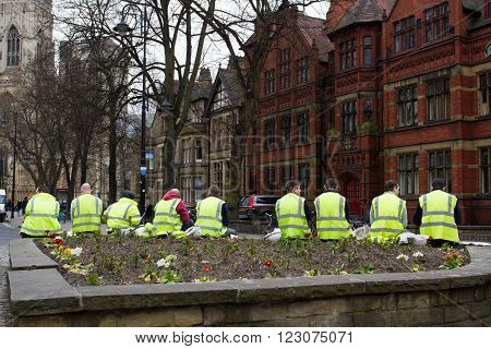 YORK, UK - MARCH 23, 2016. Workmen wearing hi-visibility clothing taking a work break in the city of York, UK.