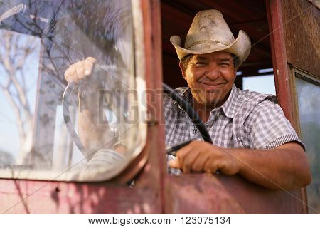 Farming and cultivations in Latin America. Portrait of middle aged hispanic farmer sitting proud in his tractor at sunset holding the steering wheel. He looks at the camera and smiles happy.