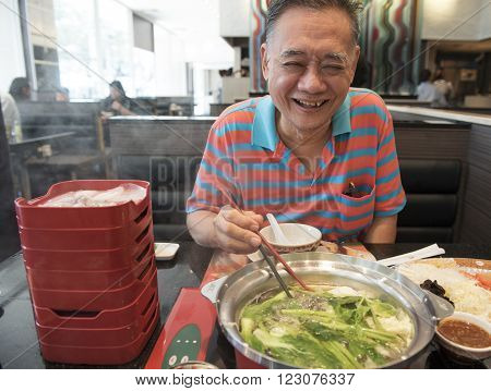 happy old man eating a shabu shabu (hot pot)