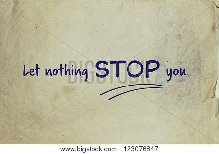 Motivational message let nothing stop you on old piece of paper