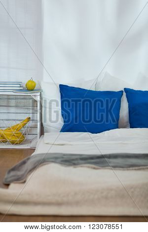 Modest simple bedroom with mattress on wooden floor and blue pillows. Wooden nightstand made of box