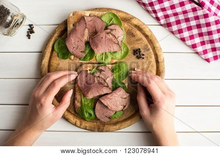 Woman holding in her hands open roast beef sandwich with salad and pepper on rustic wooden plate. Top view.