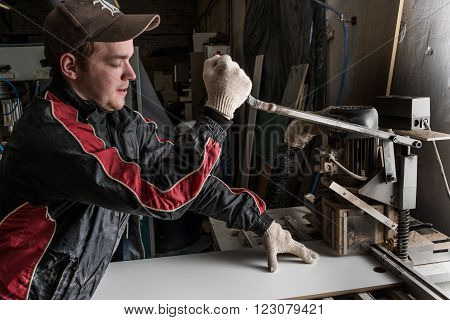 Saint-Petersburg Russia - March 17 2016: In a furniture factory carpenter making additive. The process of drilling holes in the cylindrically shaped furniture fronts (the door is) for the installation of accessories.