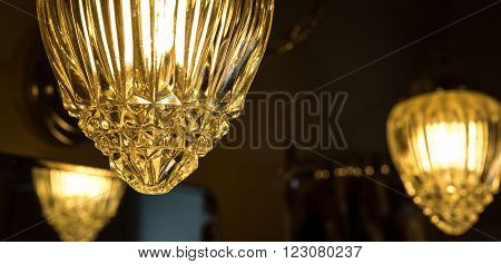 Detail of a crystal style glass cover which adorns a hanging chain link, swag style lamp in a bathroom.