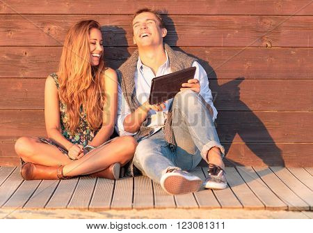 Cheerful guy with girl laugh about video on the tablet. Best friends having fun at the beach with social media and funny contents. Friendship of young people during holiday life moment at sunset.