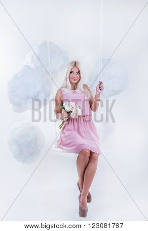 Portrait of a sexy young woman in pink dress swinging in the clouds. Studio photo
