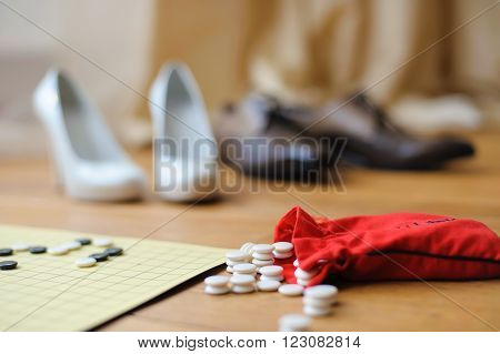 white and black stones to play go on the floor next to the board. Red bag with stones. The interior of the spacious apartments. Shoes of male and female in the background.