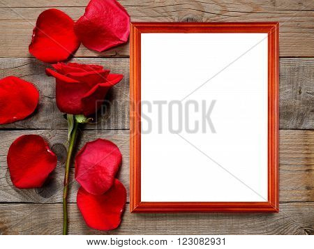 Red rose and photo frame on wooden background