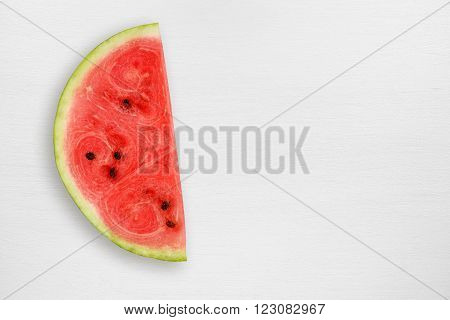 Watermelon slice on white table with copy-space