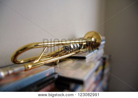 Old trumpet lays on a stack of DVD boxes in the room. Selective Focus.
