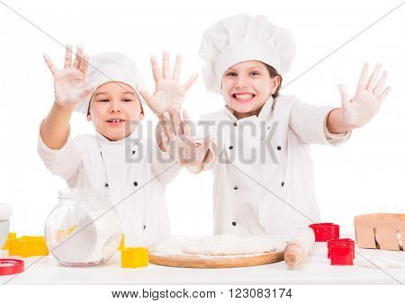 little cooks in uniform making dough with hands up