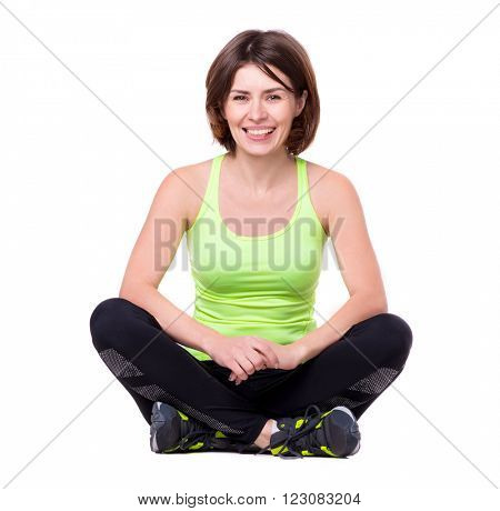 sport woman sitting on the floor with her legs crossed and resting