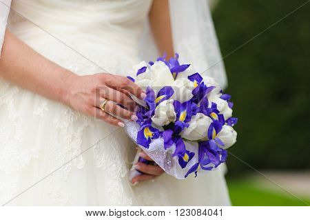 Bride holds a bouquet of tulips and irises, close up. blue irises and white tulips.