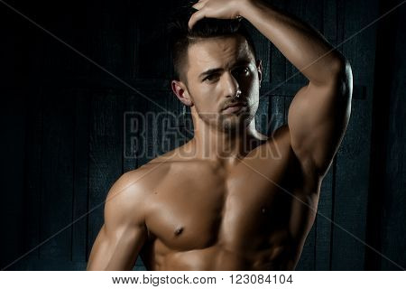 Portrait of handsome sexy sensual muscular stylish young man topless with bare torso and beautiful body standing indoor on wooden background, horizontal picture