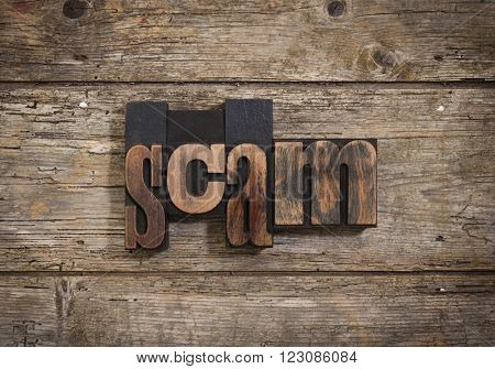 scam, single word set with vintage letterpress printing blocks on rustic wooden background