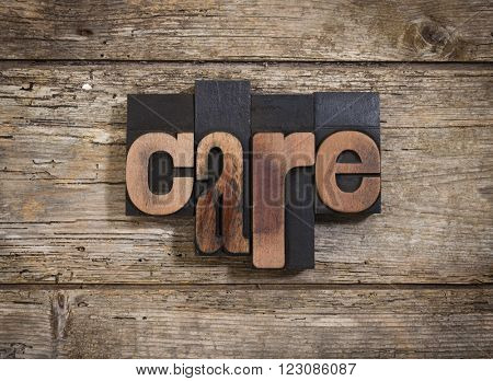 care, single word set with vintage letterpress printing blocks on rustic wooden background