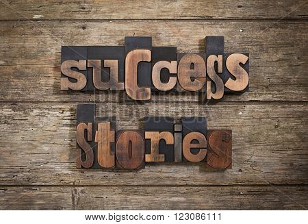 success stories, phrase set with vintage letterpress printing blocks on rustic wooden background