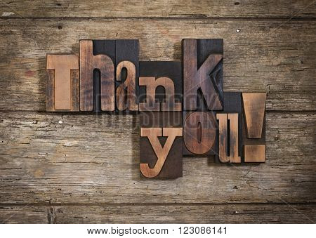 thank you, phrase set  on two lines with vintage letterpress printing blocks on rustic wooden background