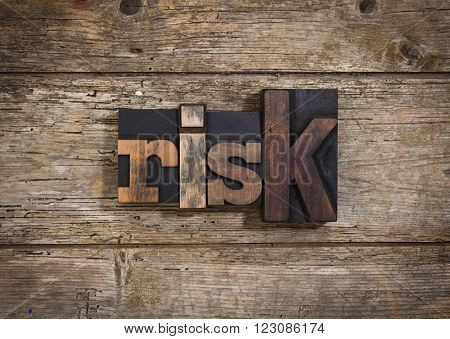 risk, single word set with vintage letterpress printing blocks on rustic wooden background