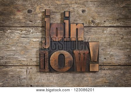 Join now, phrase set with vintage letterpress printing blocks on rustic wooden background