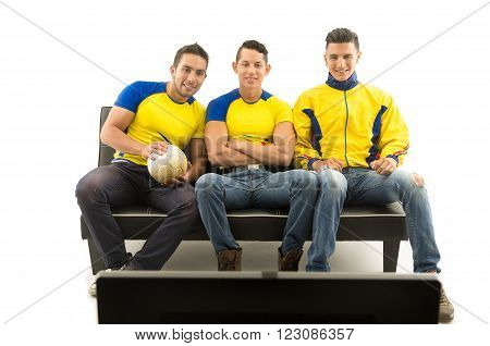 Three friends sitting on sofa wearing yellow sports shirts watching television with enthusiasm, white background, shot from behind tv.