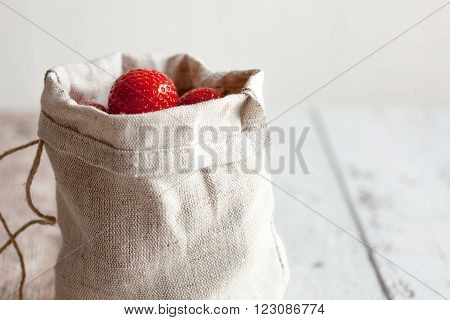 Small hessian bag of fresh strawberries on a wooden kitchen table.