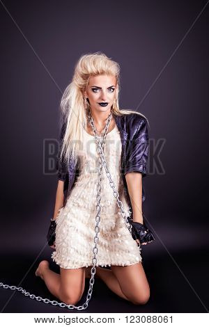 Portrait of pretty sexy young woman in leather jacket with chain. Studio photo.