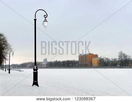 Embankment in the winter. The river which is held down by ice is brought by snow. Fog. Due to the changeable weather icicles on the plafond lamps.