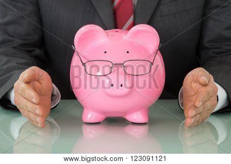 Close-up Of Businessperson Hand Near Pink Piggybank At Desk