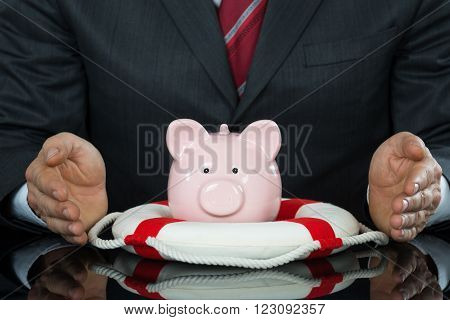 Close-up Of Businessman Hand Protecting Piggybank With Lifebelt At Desk